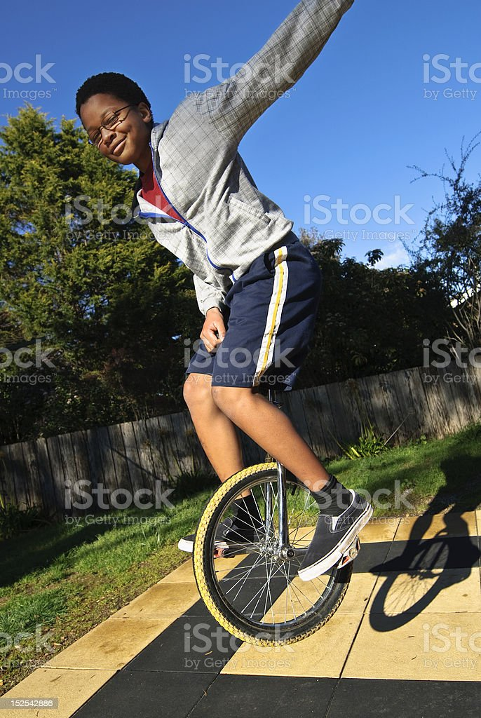 Airborne confident teenager on monocycle royalty-free stock photo