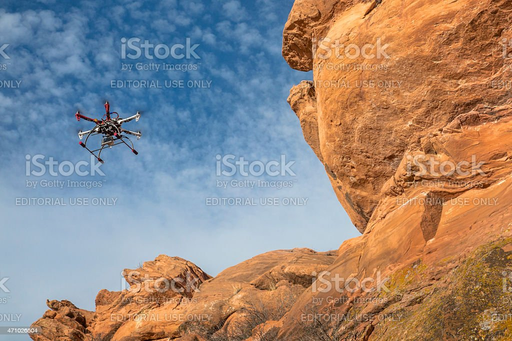 airborne hexacopter drone flying along sandstone cliff stock photo