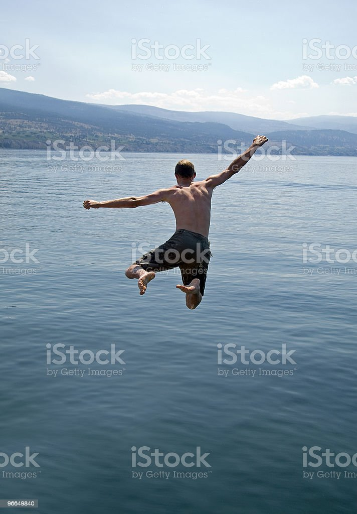 Airborne Young Man Jumping Into Lake stock photo