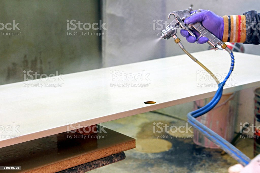 Airbrush gun sprays on wood stock photo
