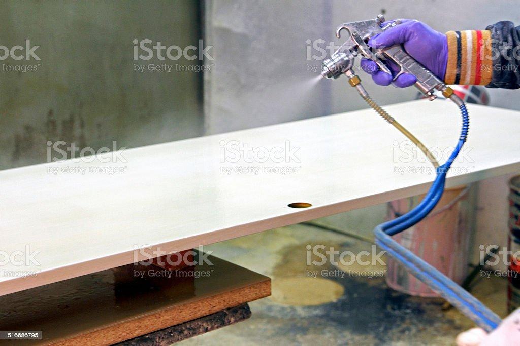 Airbrush gun sprays on wood stock photo