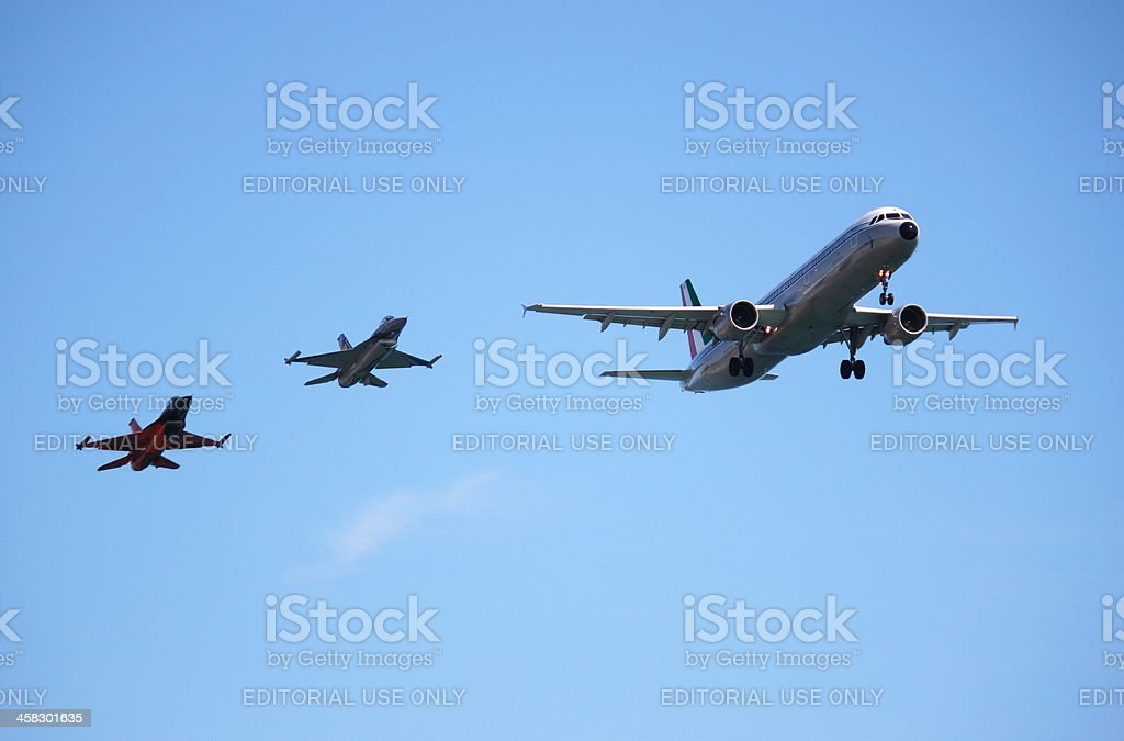 Airbus A320 aircraft accompanied by two fighters F-16 royalty-free stock photo