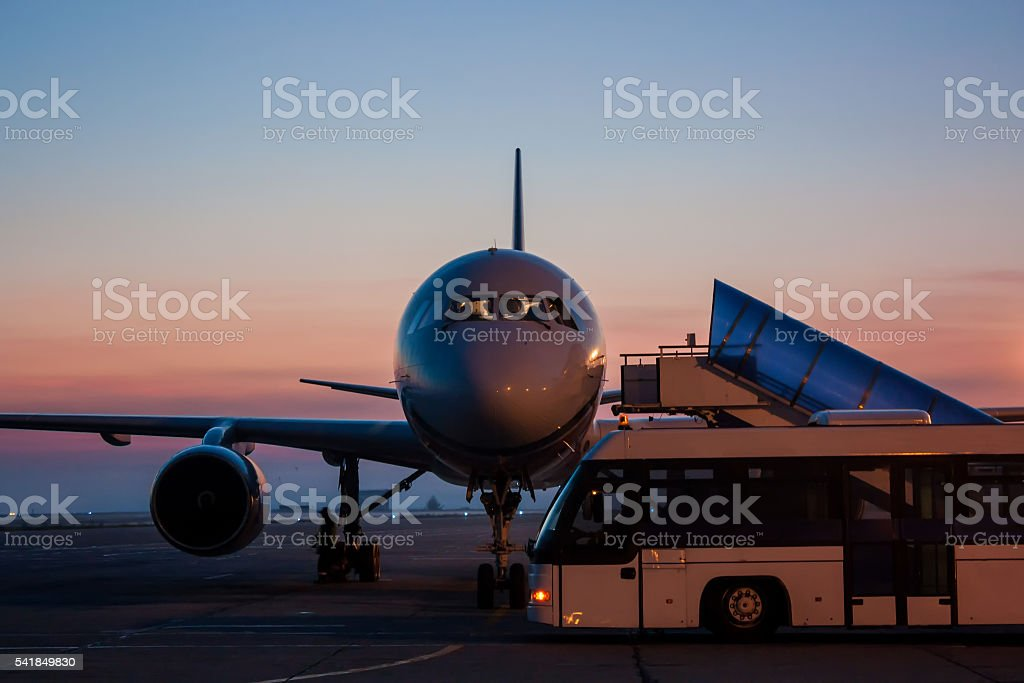 Aircraft and bus on the early morning airport apron stock photo