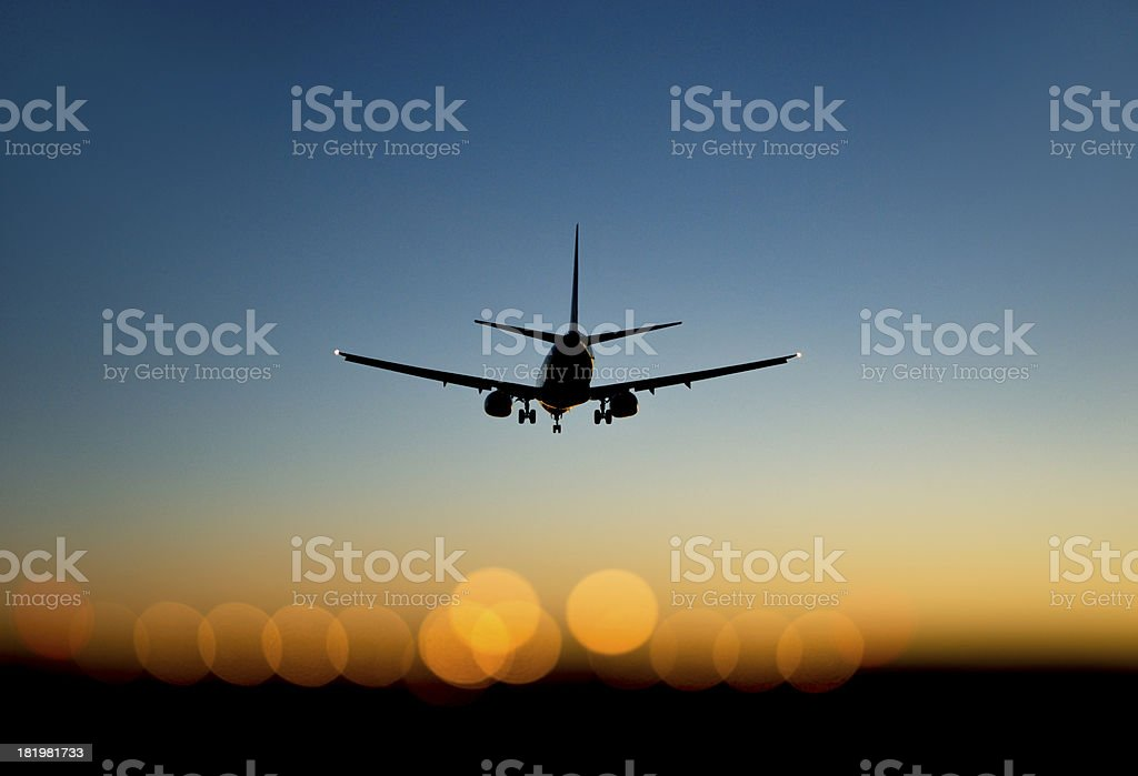 aircraft approaching airport at sunset stock photo