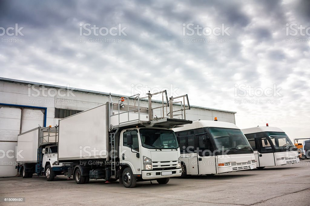 Aircraft caterers and airport buses in the parking lot royalty-free stock photo