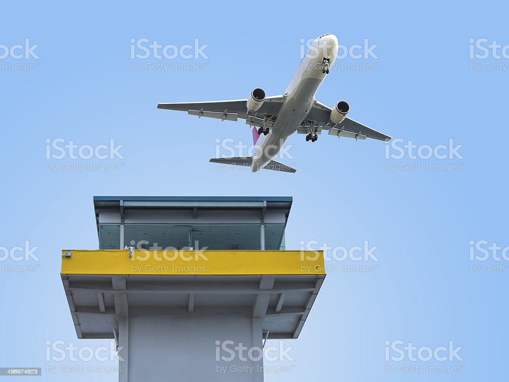 Aircraft flying over the airport control tower stock photo