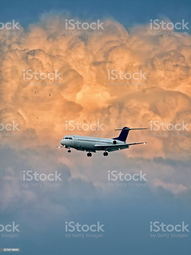 Aircraft landing with storm clouds at sunset stock photo