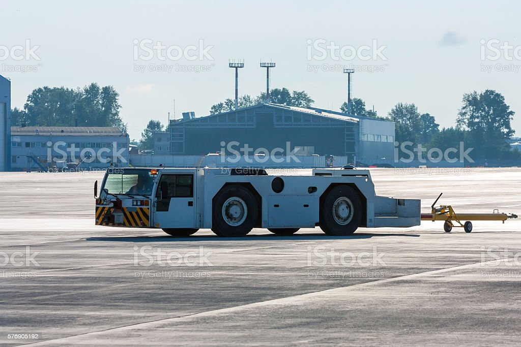 Aircraft tow tractor with moving tug on the airport apron royalty-free stock photo