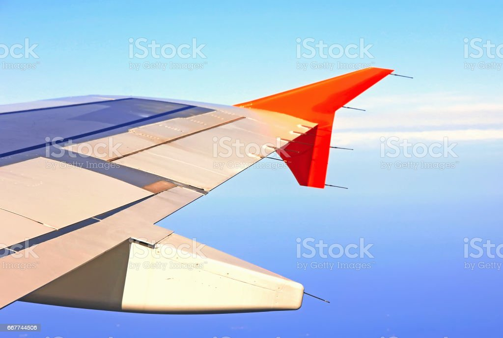 Aircraft wing in flight, view from the window at the blue sky airplane flying above the ground, soft focus stock photo