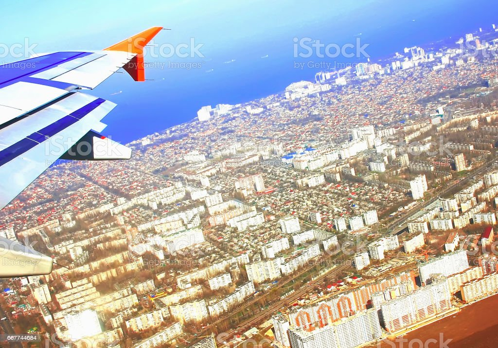 Aircraft wing in flight, view from the window of the plane flying over cities land, soft focus stock photo