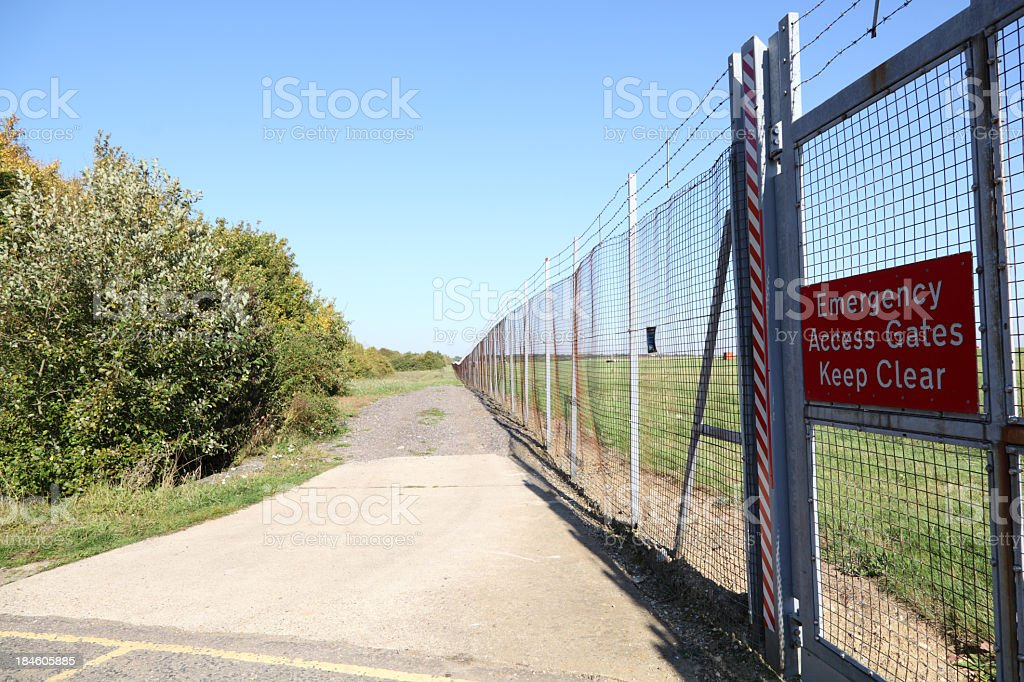 airfield perimeter security fence with warning sign stock photo