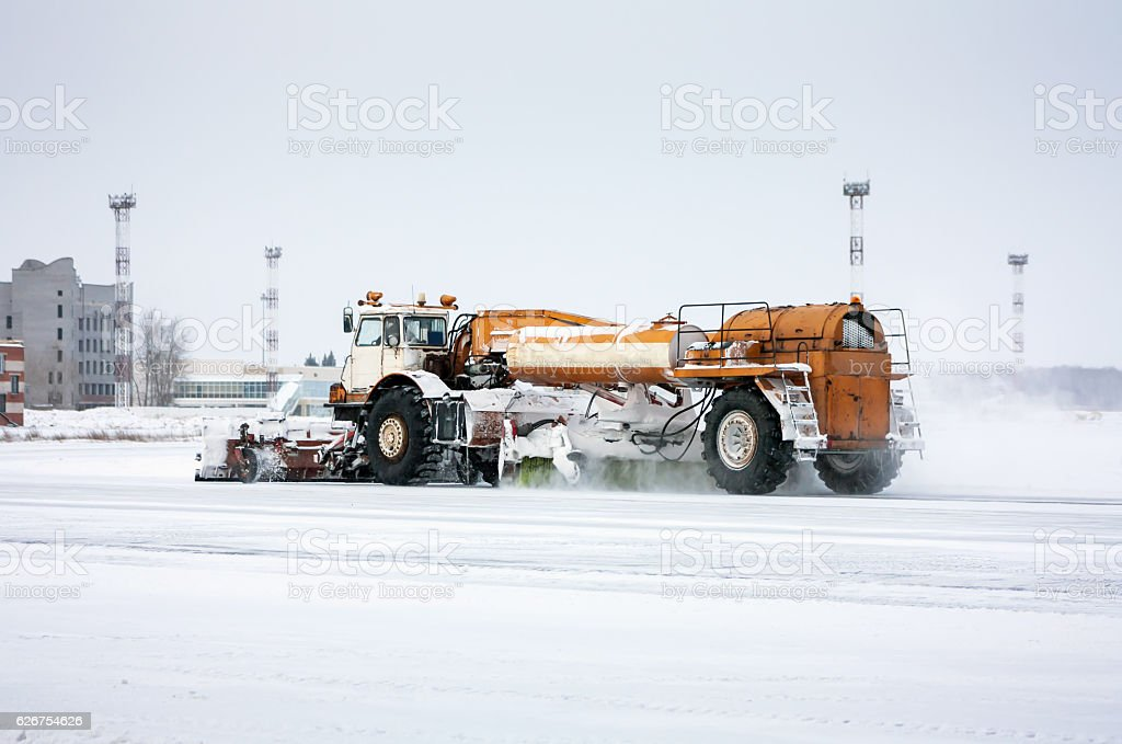 Airfield sweeper cleans the taxiway at the cold winter airport royalty-free stock photo
