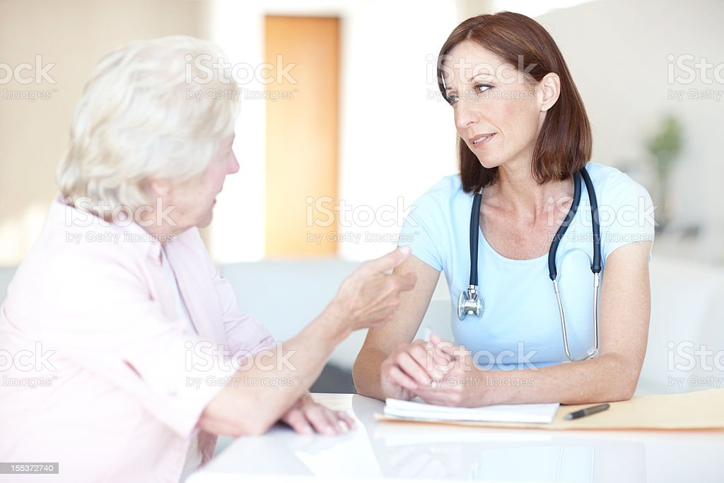 Airing her medical concerns to a trusted physician royalty-free stock photo