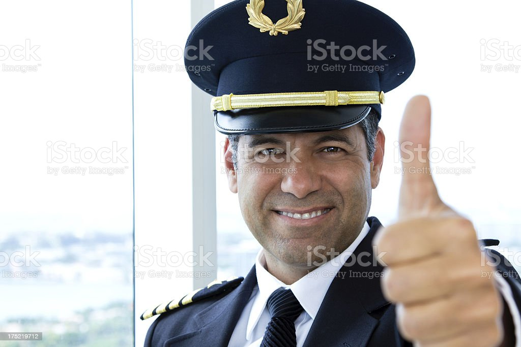 Airline pilot looking at camera giving thumbs up stock photo