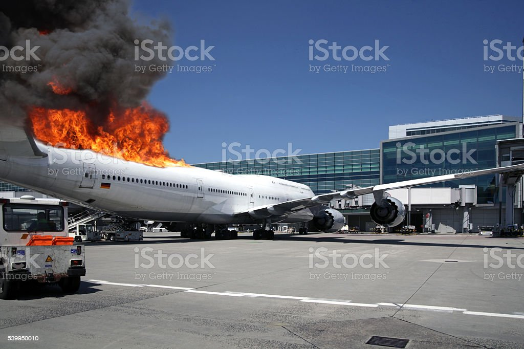 Airliner at gate engulfed in fake flames stock photo