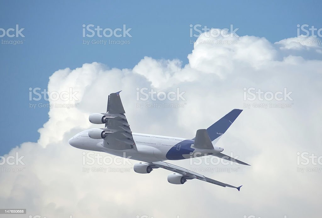 airliner flying away over clouds stock photo