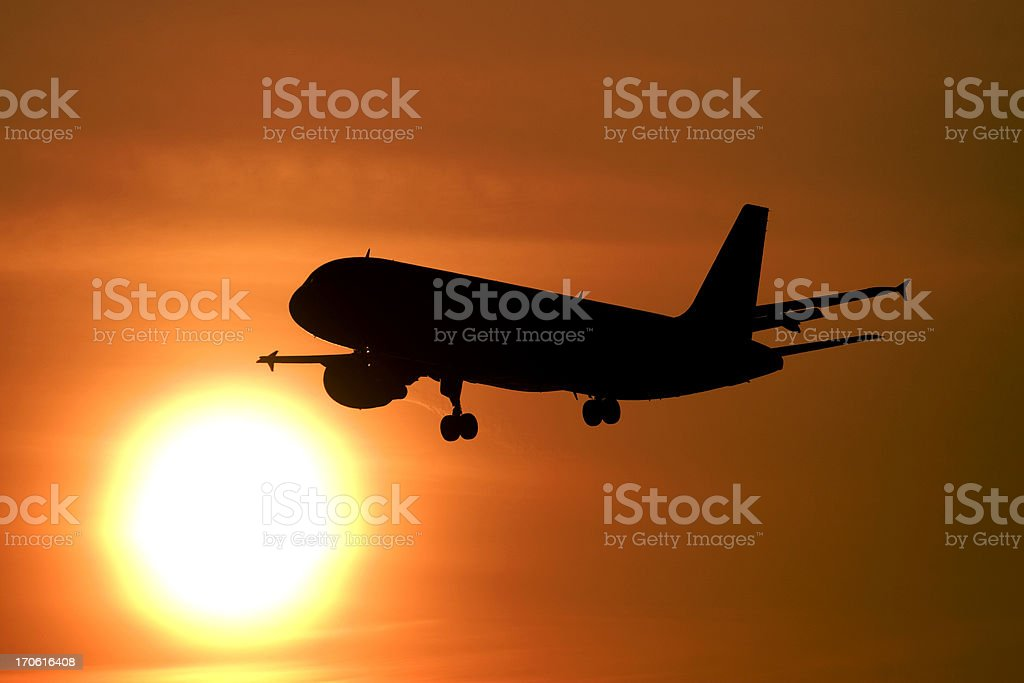 Airliner flying into the sun stock photo
