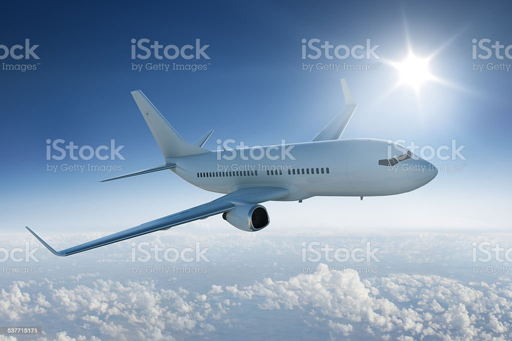 Airliner flying past the sun - in blue sky stock photo
