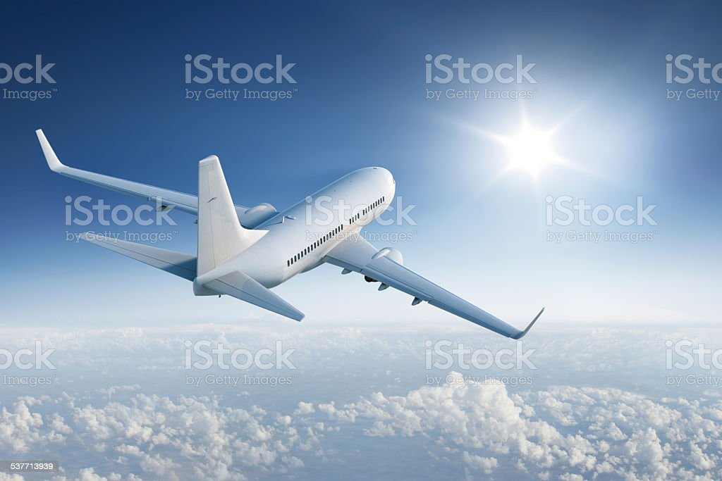 Airliner flying towards the sun in blue sky stock photo