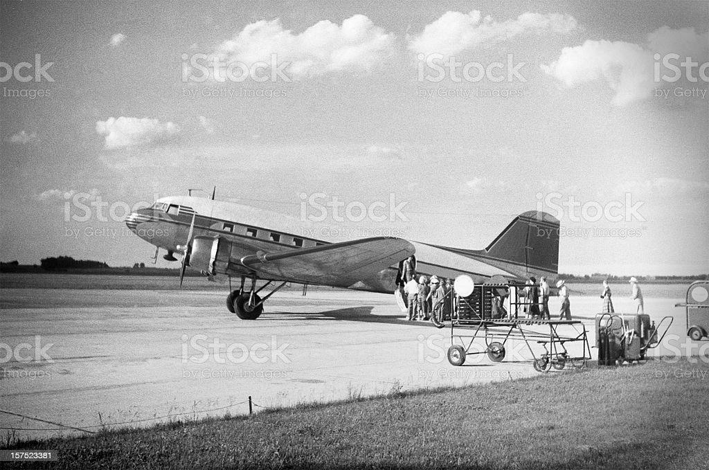 DC-3 airliner loading passengers 1951, retro stock photo