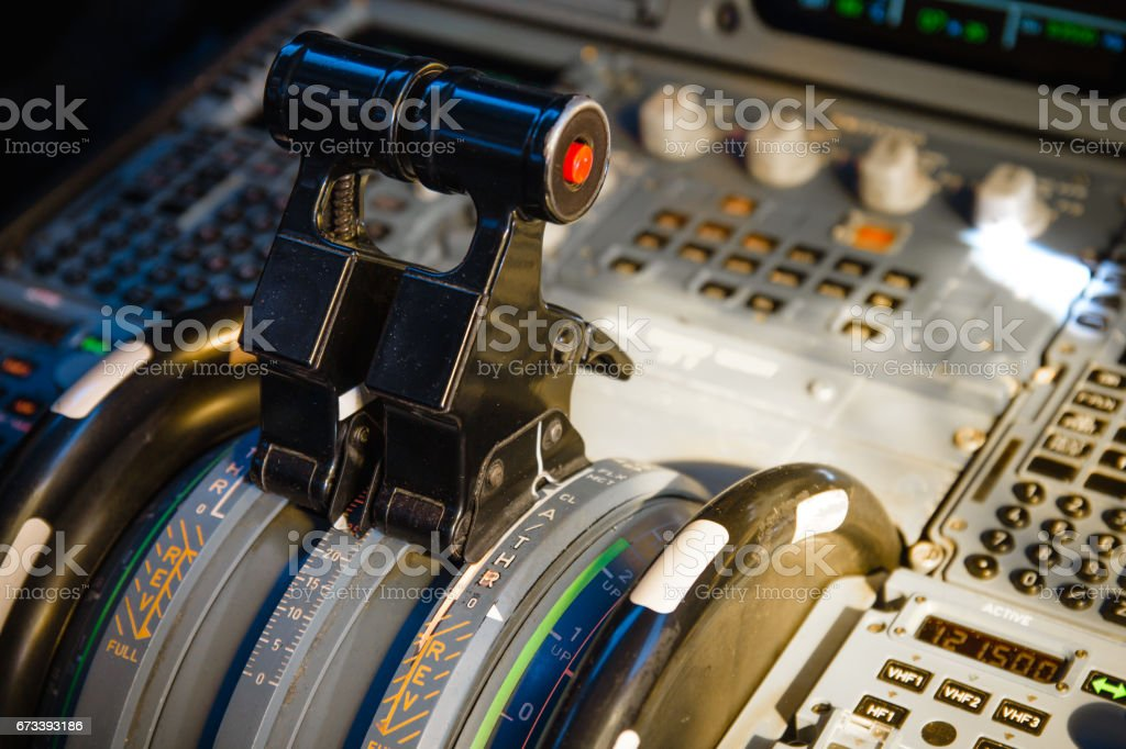 Airliner thrust levers on the centre pedestal instrument panel. Switches and dials visible in the background. stock photo