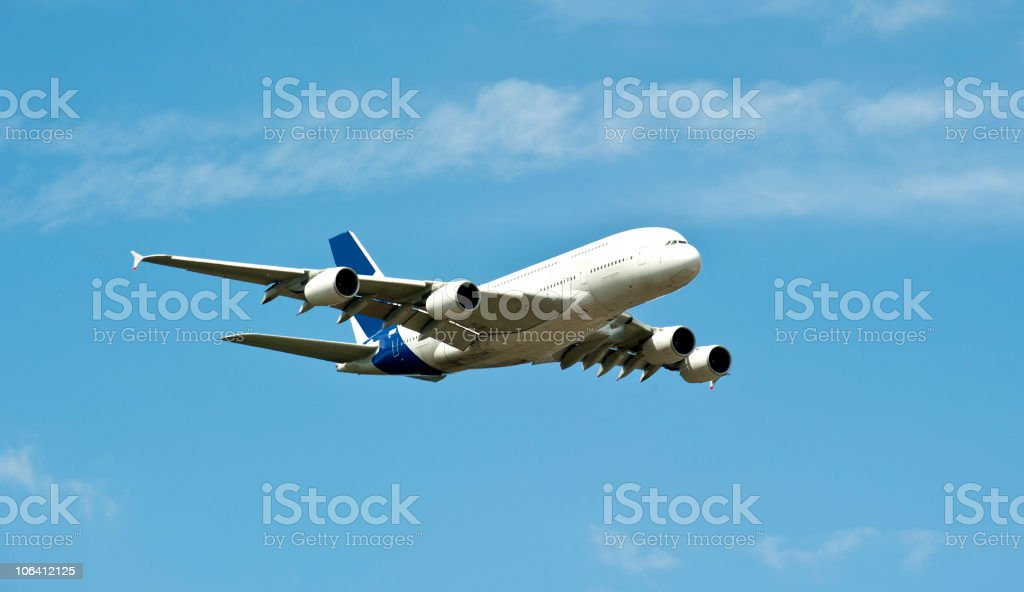 Airplane A380 flying through blue skies stock photo