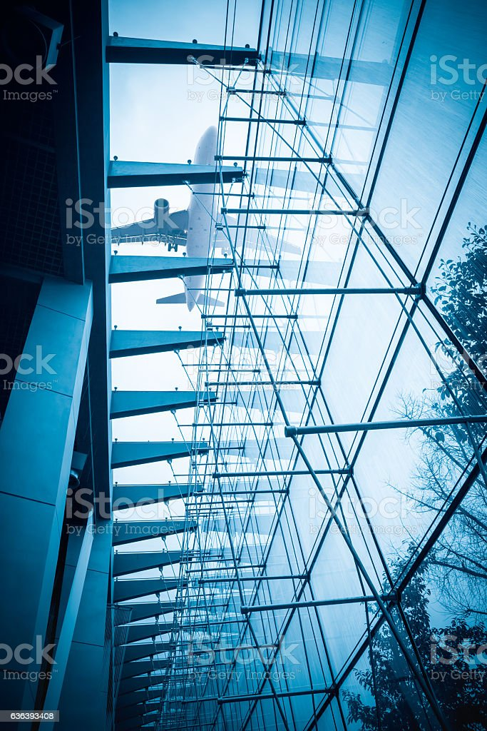 airplane above the glass building stock photo