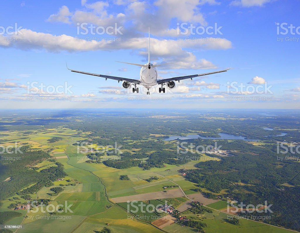 Airplane against cloudy blue sky royalty-free stock photo