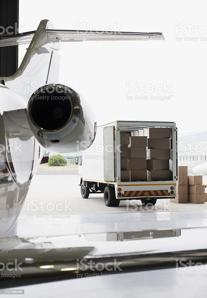 Airplane and truck being loaded with boxes royalty-free stock photo