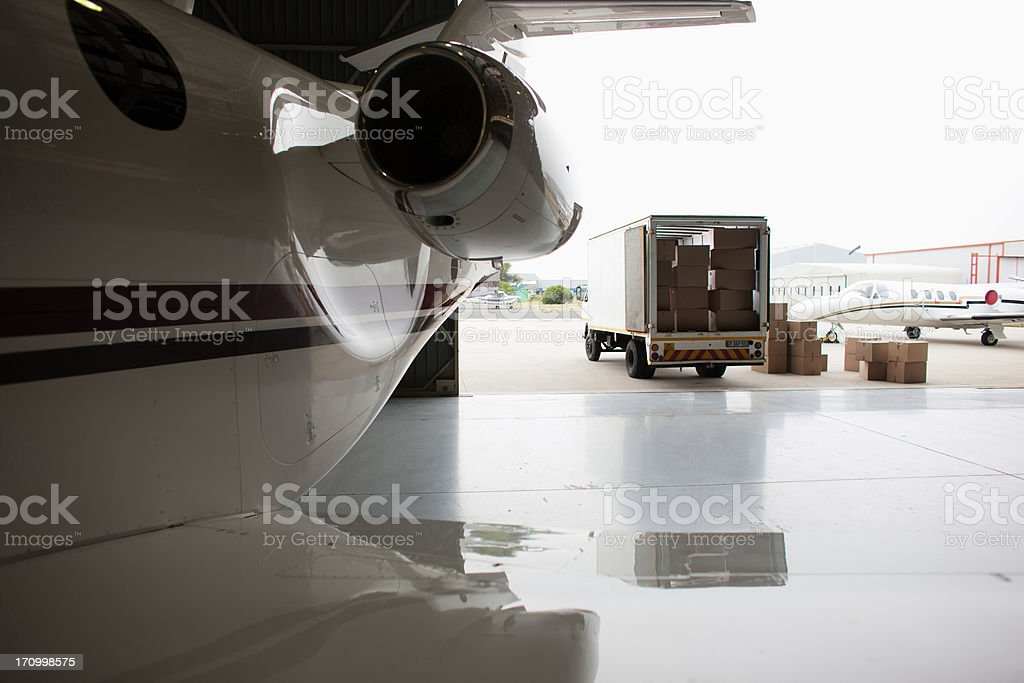 Airplane and truck being loaded with boxes stock photo