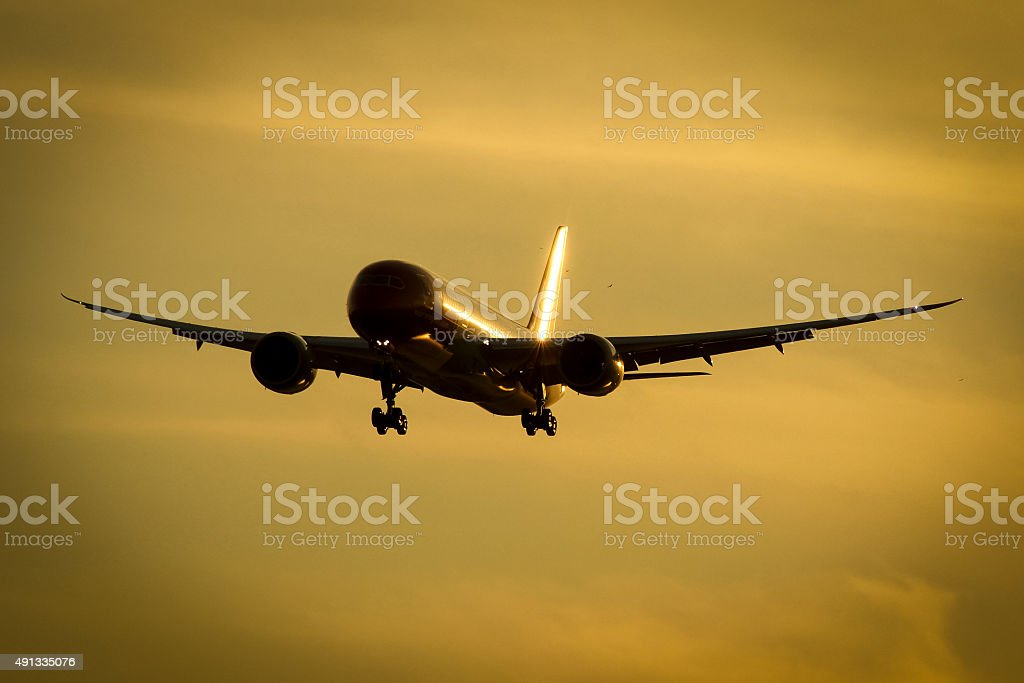 Airplane approach at sunset stock photo