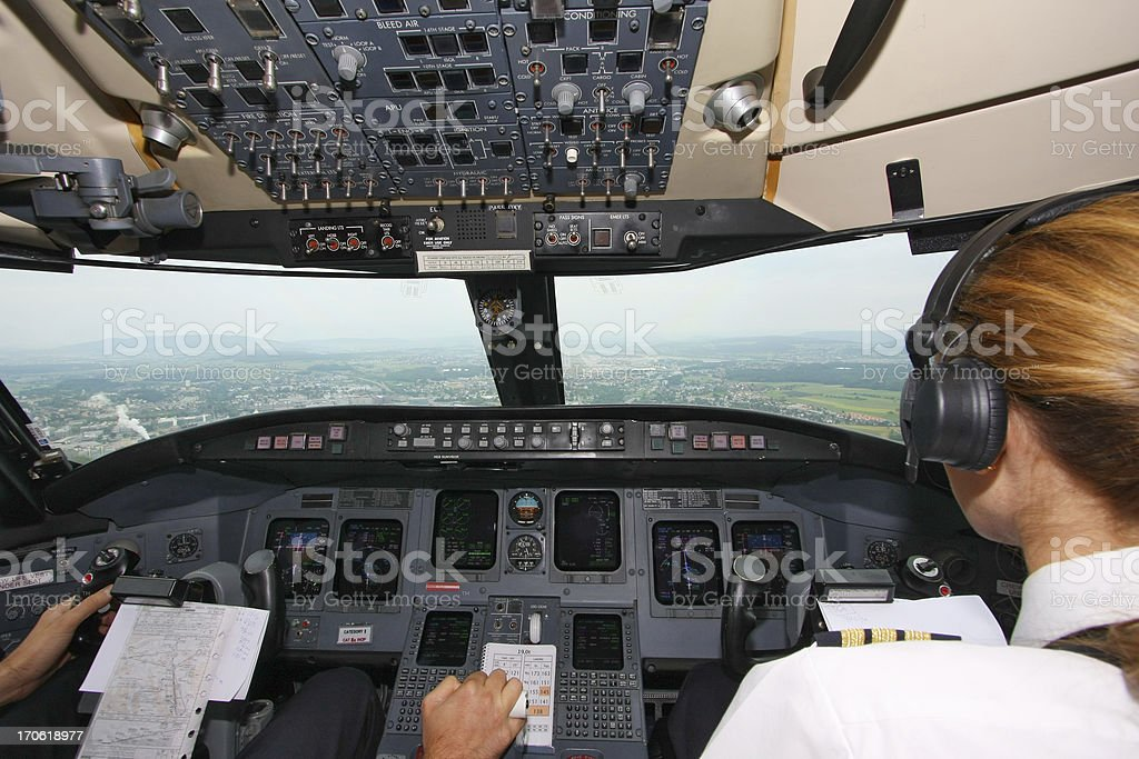 Airplane approaching the airport...pilots in cockpit royalty-free stock photo