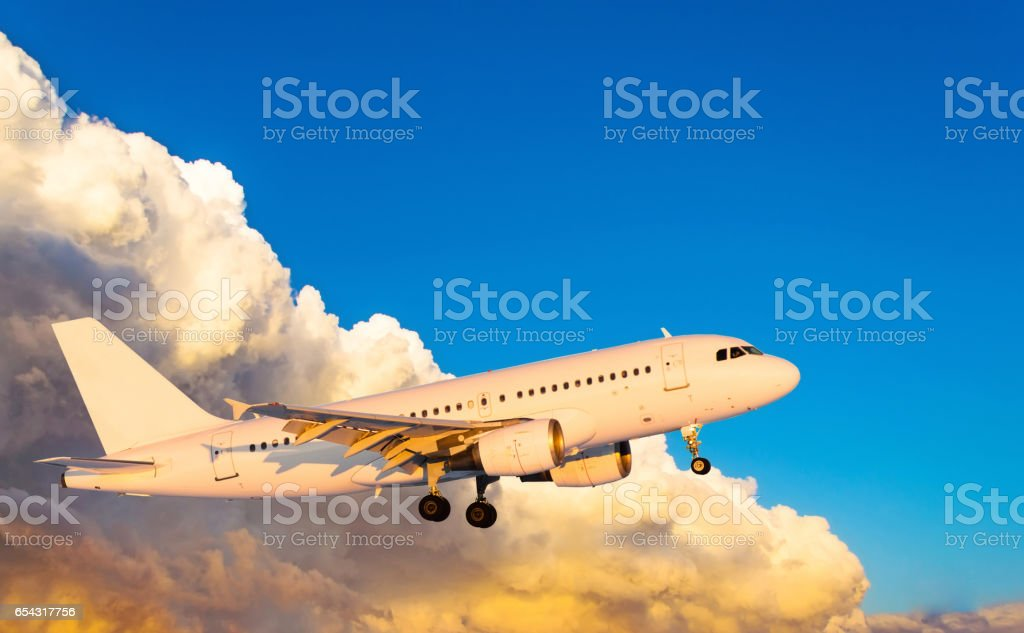 Airplane at fly on the sky with clouds sunset stock photo