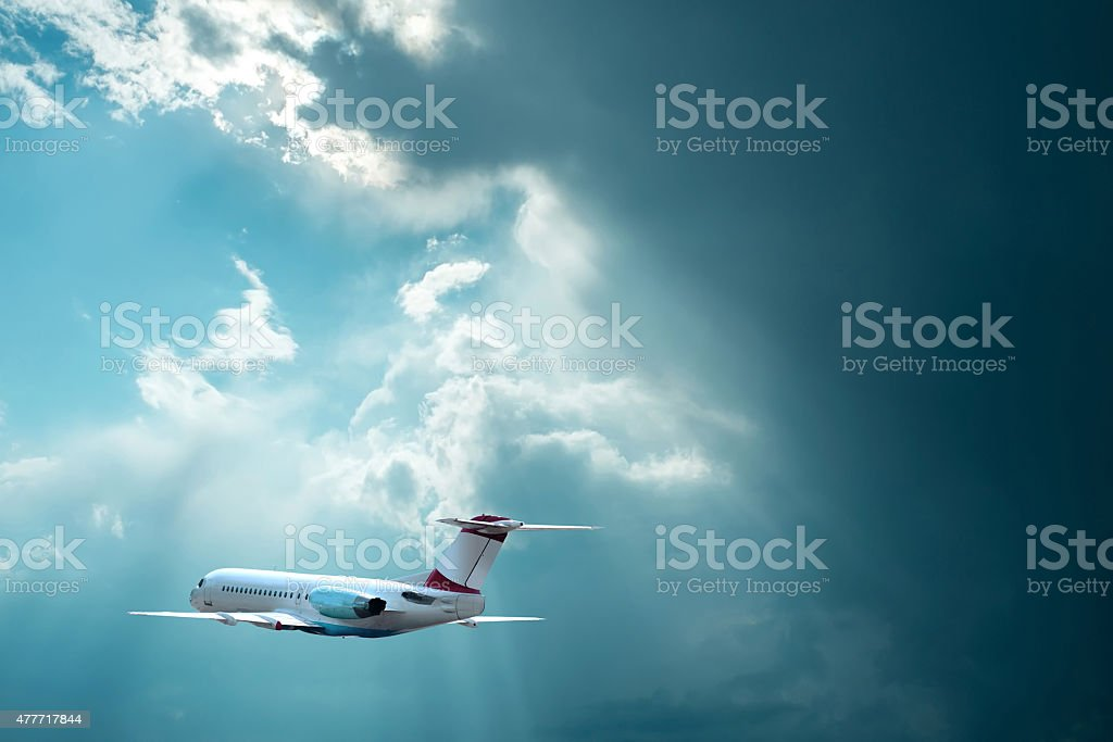 Airplane at flying under sky with clouds stock photo