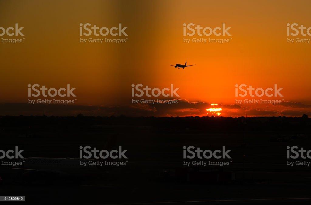 Airplane at sunrise stock photo
