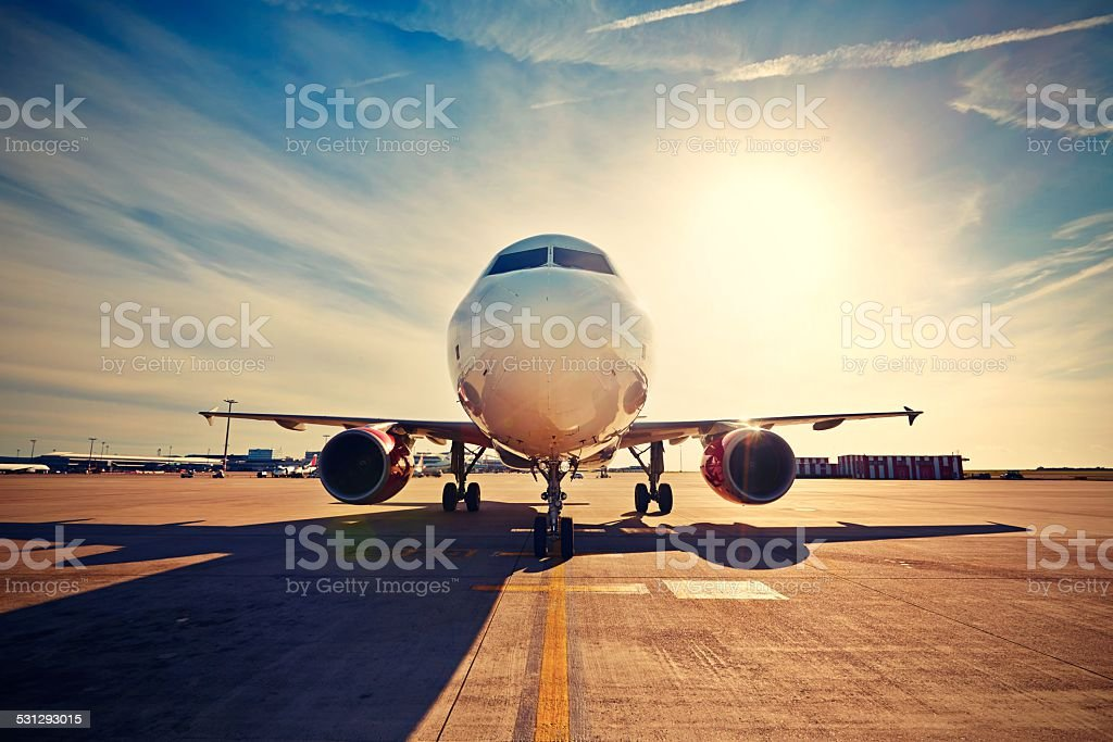 Airplane at the sunrise stock photo