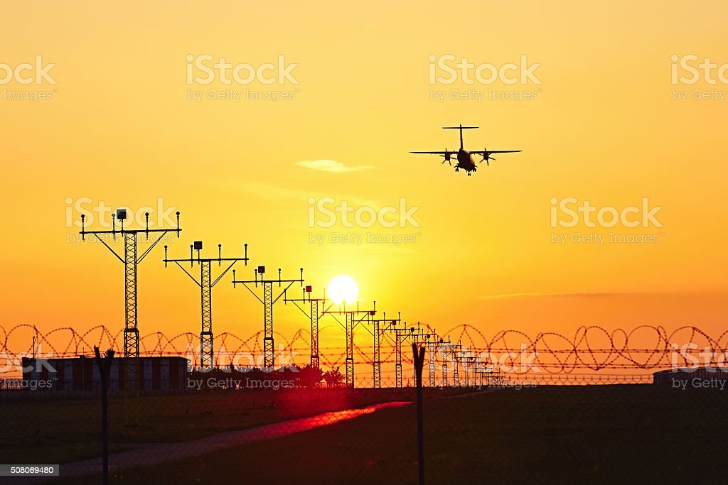 Airplane at the sunset stock photo