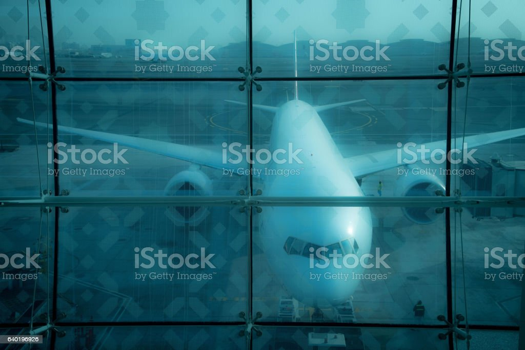 Airplane behind glass at the airport stock photo