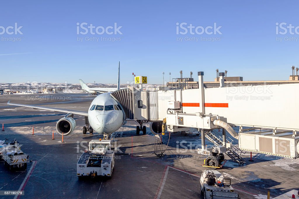 Airplane Being Serviced at Airport Gate stock photo