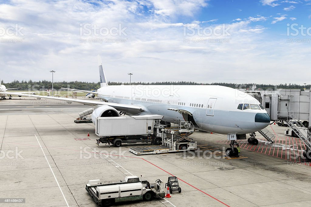 Airplane Being Serviced at the Gate of an International Airport stock photo