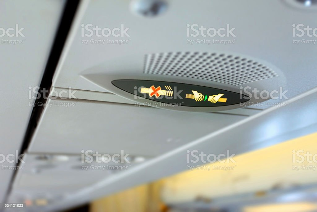 Airplane cabin, seat belt and no smoking sign stock photo
