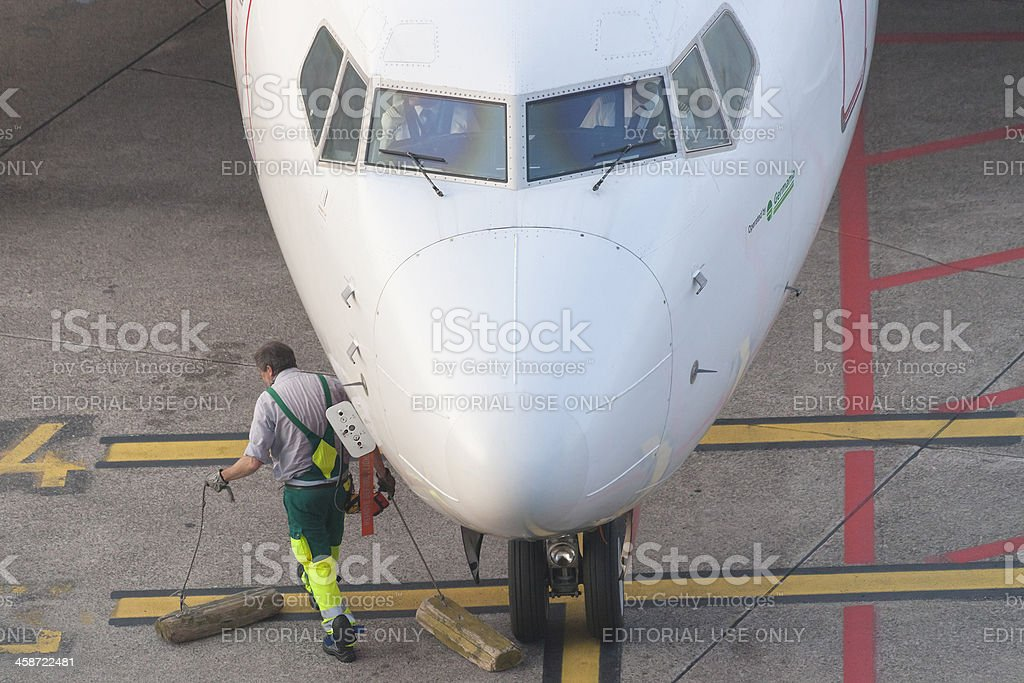 Airplane cockpit and ground technician on airport stock photo