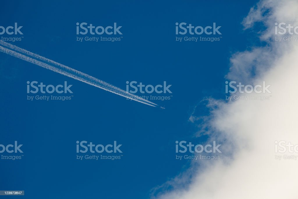 Airplane, condensation path, and cloud royalty-free stock photo
