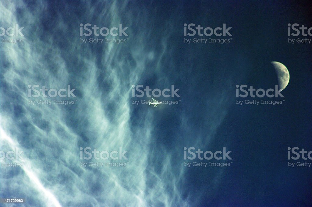 Airplane crossing the moon royalty-free stock photo
