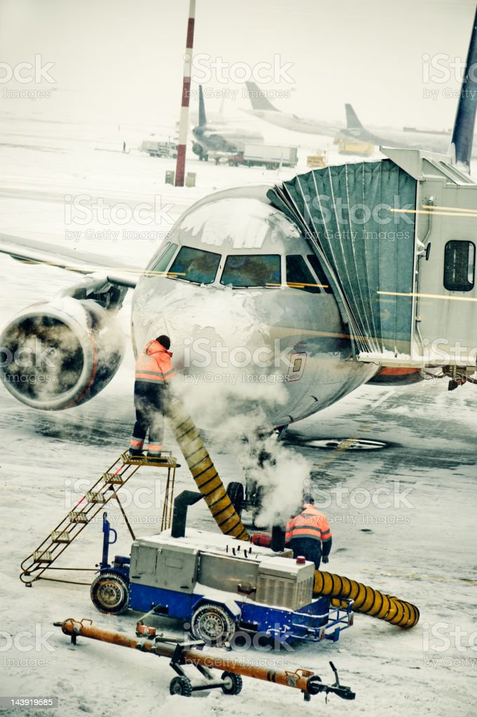 Airplane de-iced after snowstorm stock photo