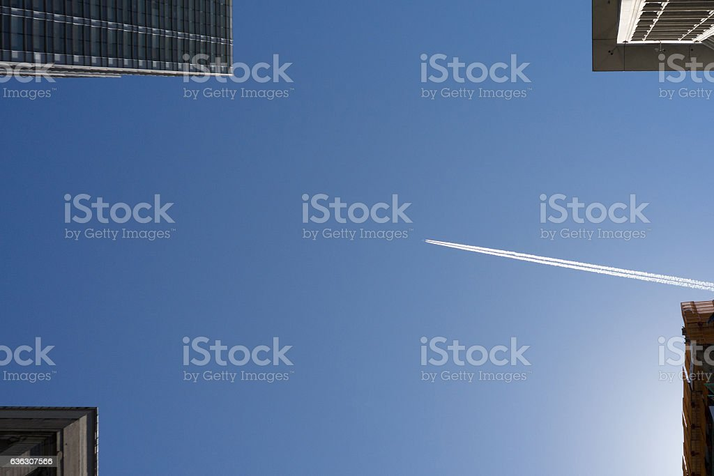 airplane flies high above the city stock photo