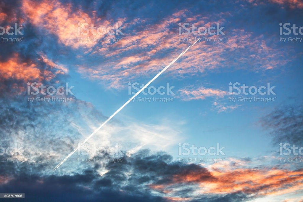Airplane flies in sunset dramatic clouds and leaving trail stock photo