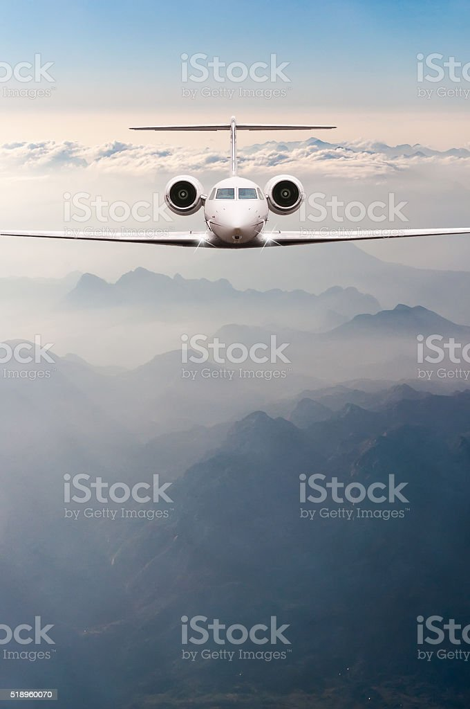 Airplane fly over clouds and Alps mountain on sunset. Front stock photo