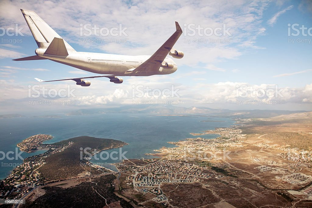 airplane flying above a seaside city stock photo