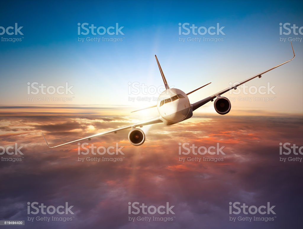 Airplane flying above clouds in dramatic sunset stock photo